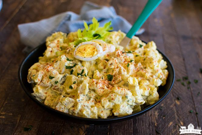 a bowl of potato salad garnished with hard boiled eggs