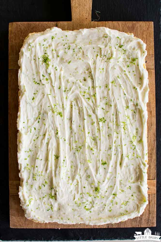 frosted sugar cookie bars with lime zest on a wooden cutting board