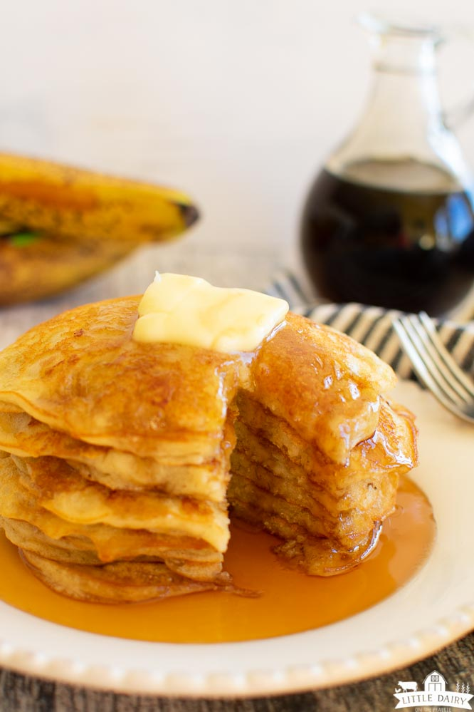 a stack of banana pancakes with a wedge cut out of them and a pat of butter on top with syrup drizzled over