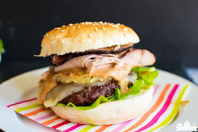 a beef burger with pineapple rings, deli ham, creamy sauce, and lettuce on a striped napkin