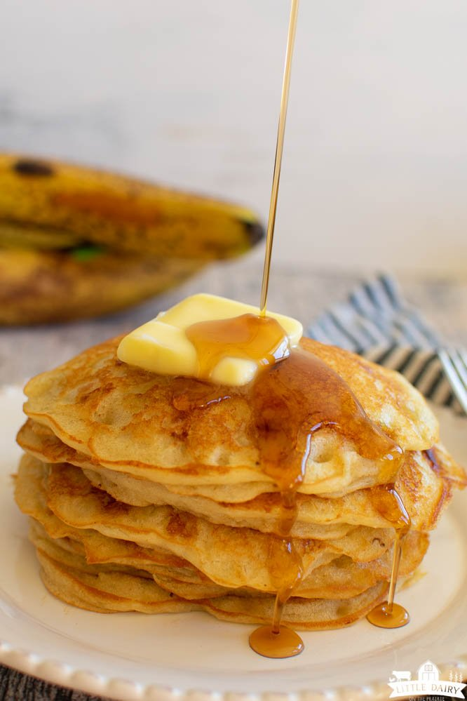 a stack of pancakes with a pat of butter on top, maple syrup being drizzled over the top