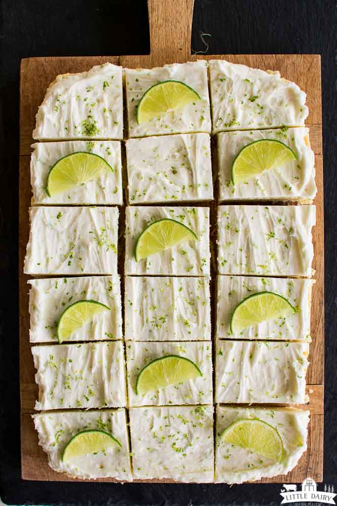 a wooden cutting board with cookies cut into squares, and topped with fresh lime wedges