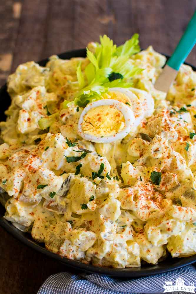 a bowl of creamy salad with pickles, potatoes, and fresh herbs