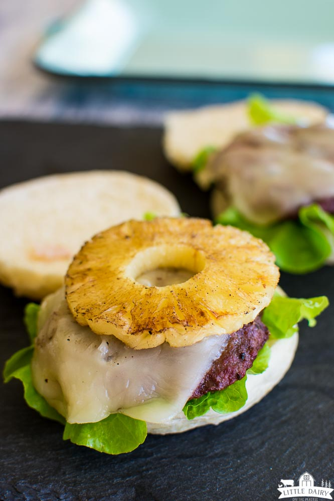 a hamburger bun topped with lettuce, a burger patty, melted cheese, a grilled pineapple ring