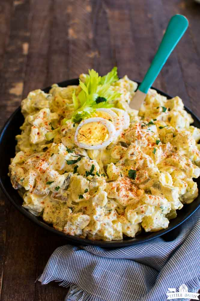 a bowl of salad made with potatoes and hard boiled eggs on top