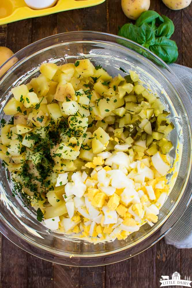 a clear bowl with diced potatoes, chopped hard boiled eggs, and green herbs