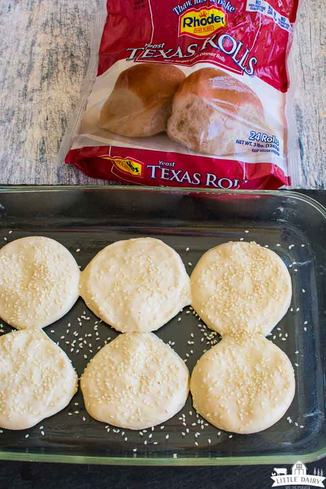 dough shaped into hamburger buns, sprinkled with sesame seeds, and a bag of Rhodes Texas sized rolls.