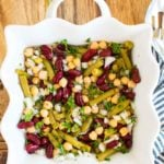 a white dish with kidney beans, garbanzo beans, and green beans in an italian dressing