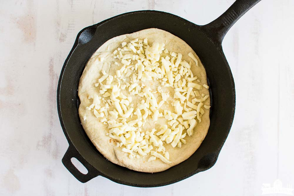 a flour tortilla in a cast iron skillet with grated mozzarella cheese