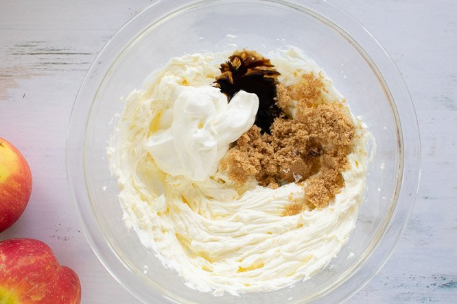 a glass bowl filled with beaten cream cheese, vanilla, sour cream, and brown sugar