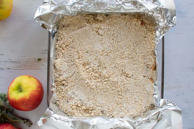 a baking pan filled with apple crumb bars and and apple