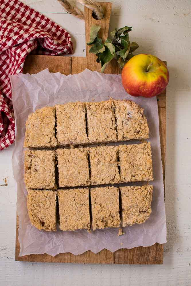 a wooden cutting board with apple crumb squares on top of a white piece of paper and an apple