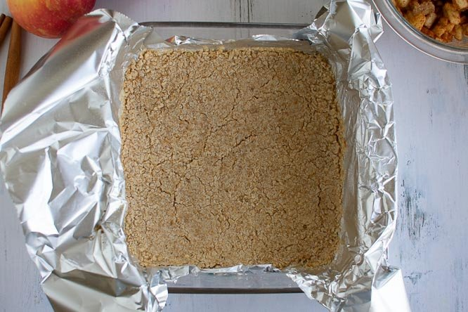 a square glass baking pan lined with foil and filled with crumb crust