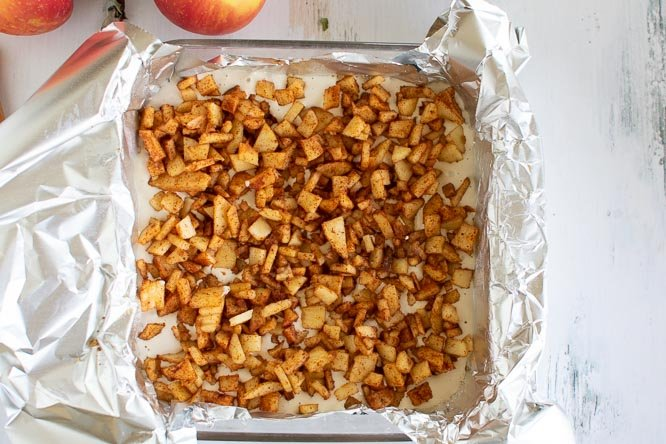 a foil lined glass pan filled with chopped cinnamon apples on top of cheesecake