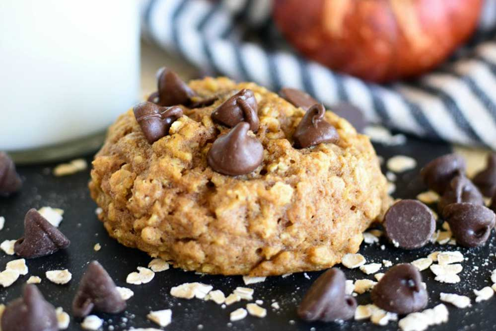 a pumpkin cookie with chocolate chips on top and oatmeal scattered around it