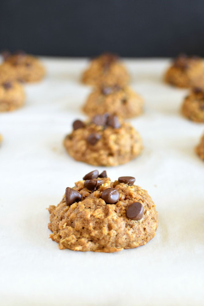 a baking sheet lined with parchment paper and topped with baked pumpkin cookies with chocolate chips and oatmeal