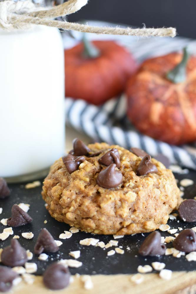 a black paper topped with a baked pumpkin cookie with chocolate chips