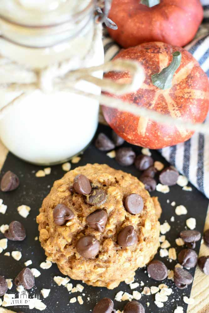 Birds eye view of a chocolate chip cookie with pumpkin and oatmeal, plus two pumpkins and a glass of milk