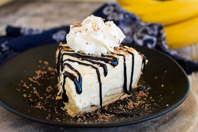 a slice of creamy pie on a black plate with whipped cream and chocolate drizzle