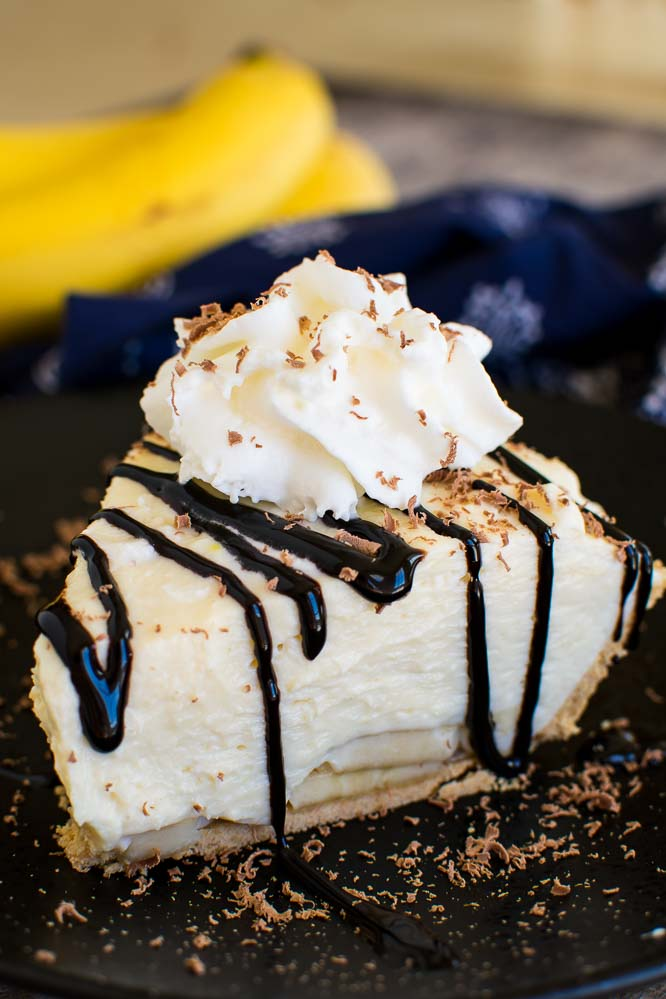 a piece of banana cream pie with a graham cracker crust, chocolate drizzle, and whipped cream on top