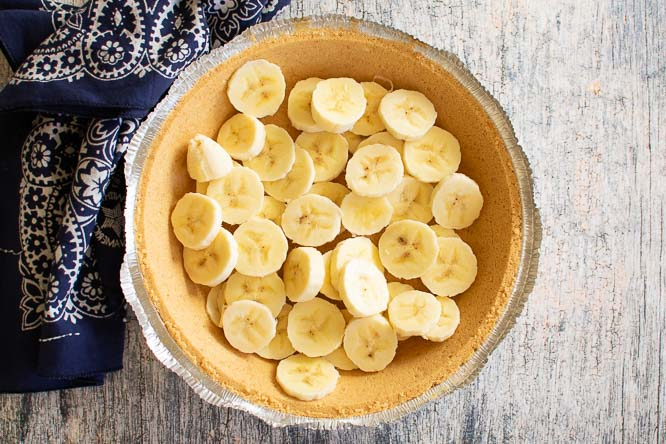 a graham cracker crust with sliced bananas in it