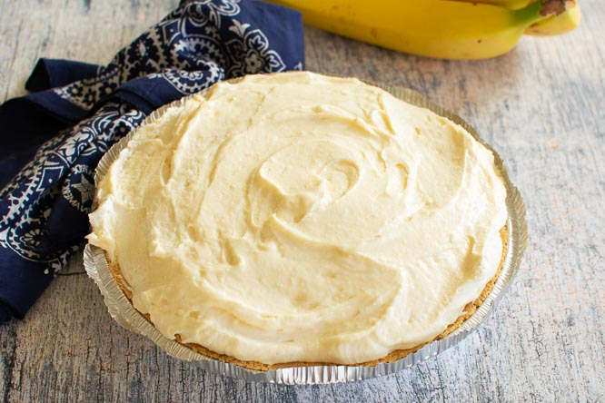 a no bake pie in a graham cracker crust with a bunch of bananas in the background