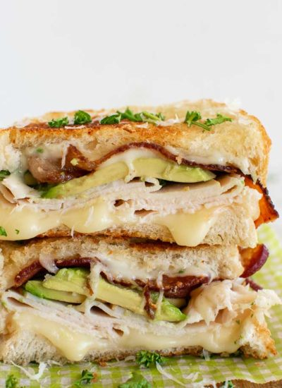 a hot turkey sandwich cut in half and topped with avocado, turkey, and bacon