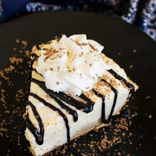 Top view of a piece of banana cream pie with chocolate drizzle on a black plate