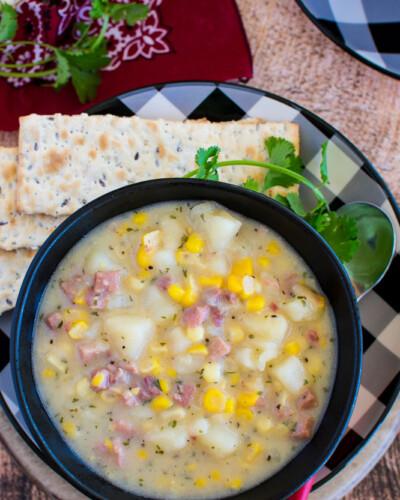 A black bowl with diced potato, ham, and corn soup.