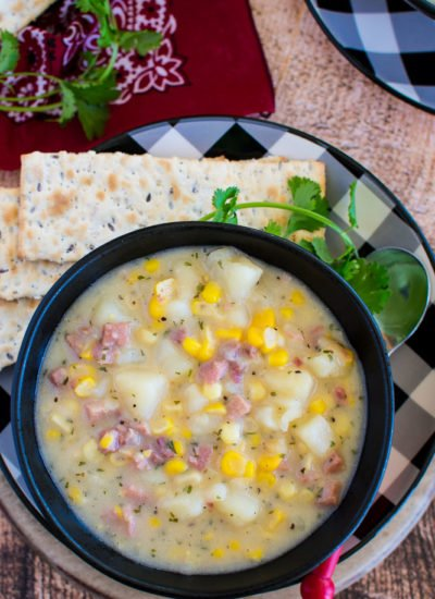 A black bowl with diced potato, ham, and corn soup.