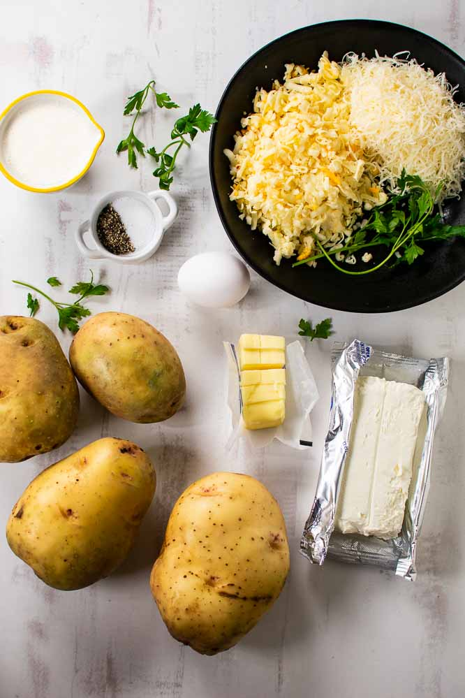 whole potatoes, grated cheese in a bowl, cream cheese, butter, salt and pepper, an egg, and a measuring cup with whole milk. Fresh parsley.