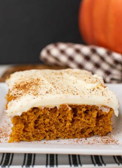a pumpkin square on a white plate with cream cheese icing, sprinkled with ground nutmeg