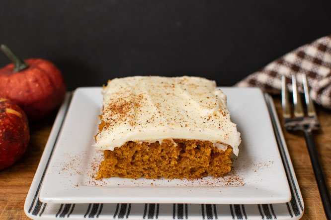 a pumpkin bar on a white plate, cream cheese frosting and garnished with ground nutmeg
