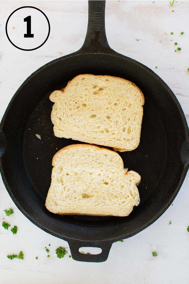 a cast iron skillet with two pieces of bread in it