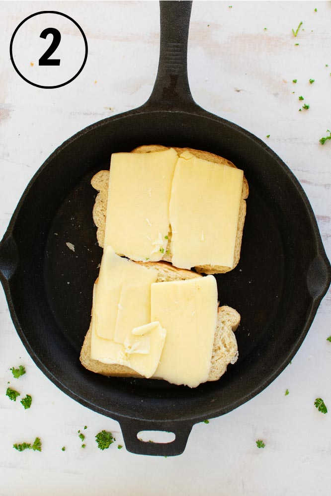 two slices of bread in a cast iron skillet topped with sliced mozzarella cheese