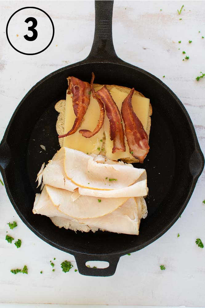 a cast iron skillet with deli turkey on on piece of bread and cheese and slices of bacon on the other half