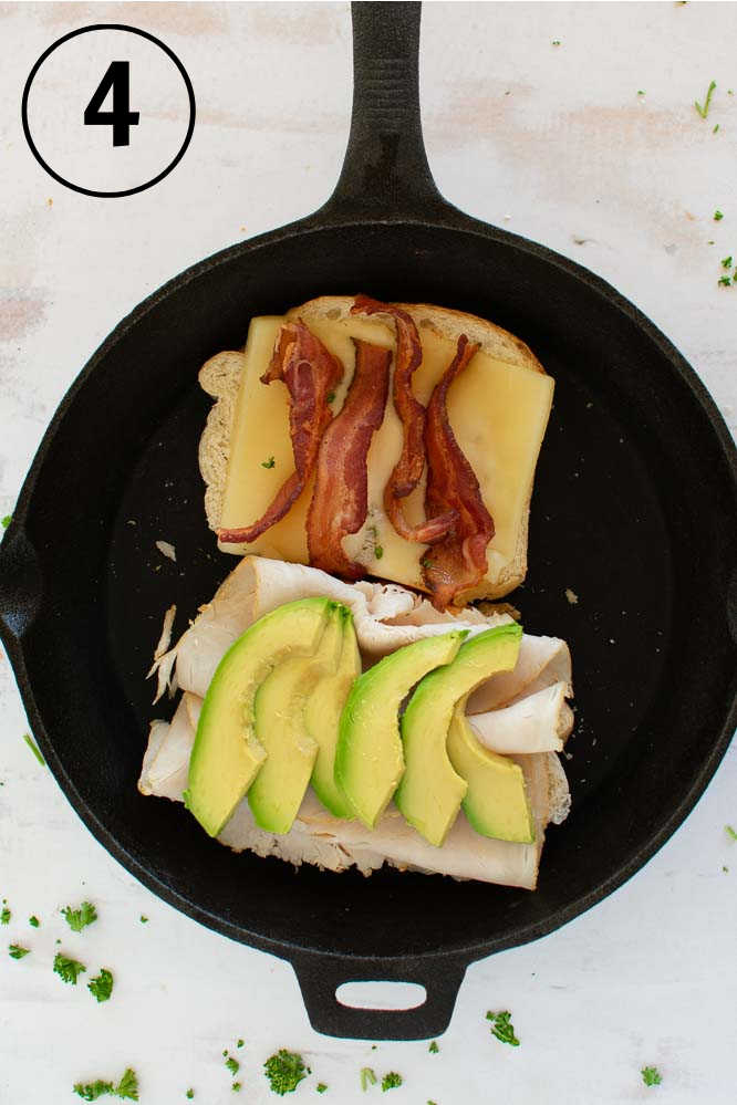a cast iron skillet with a grilled cheese sandwich with turkey, bacon slices, and avocados