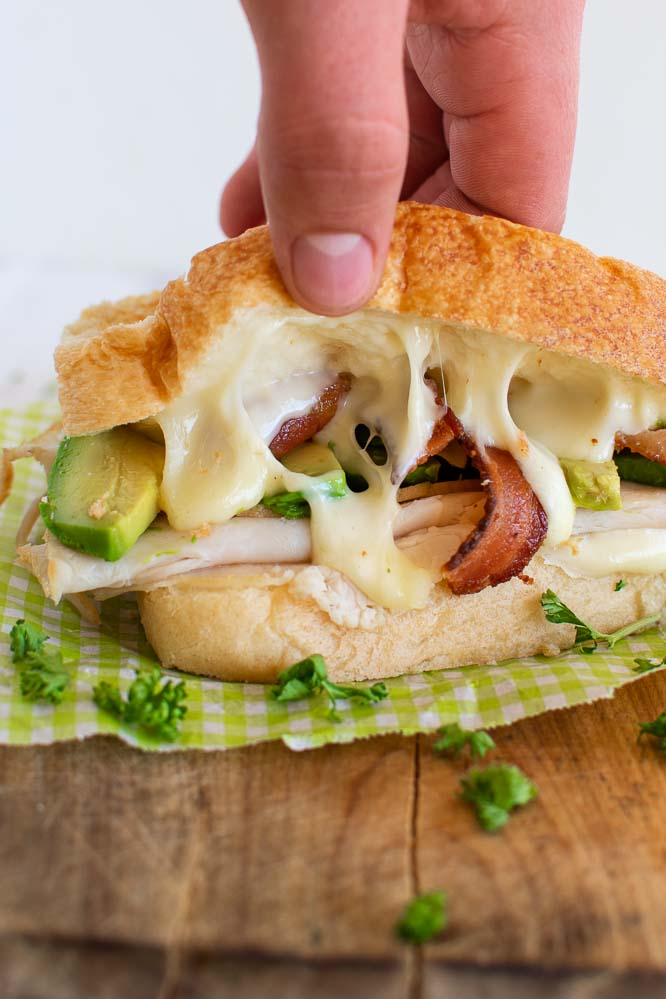 Grilled turkey melt being pulled apart with bacon and avocado inside