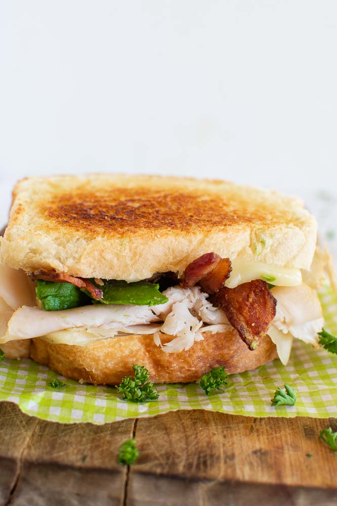 A grilled turkey sandwich with melted cheese and with sliced deli turkey, avocados, and bacon