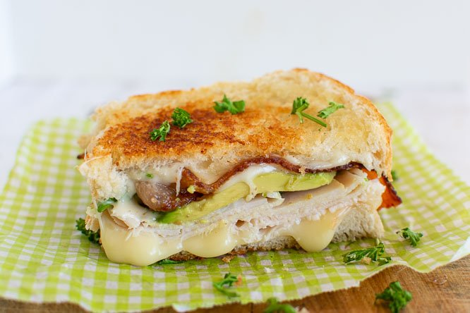 a grilled turkey sandwich with cheese, avocado, bacon on a white and green parchment paper