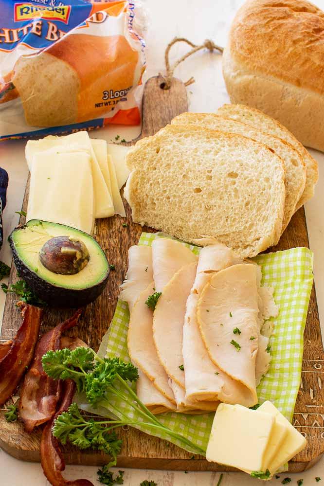ingredients to make turkey sandwiches; sliced white bread, avocado, bacon, sliced turkey, mozzarella cheese, sliced butter