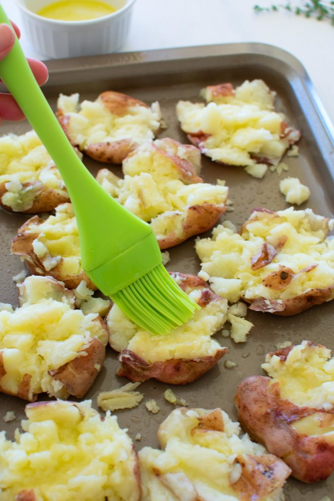 Smashed red potatoes being brushed with melted butter.