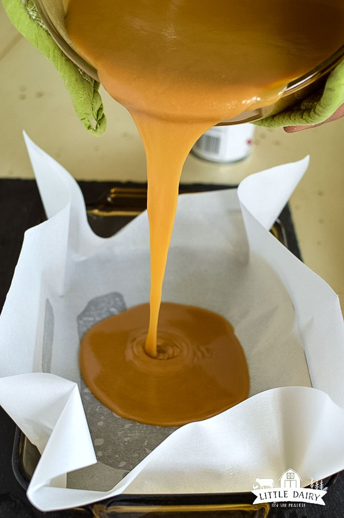 Warm caramel sauce being poured in a pan.