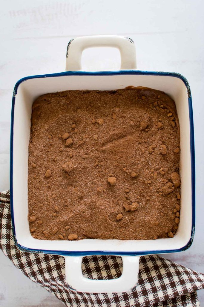 An unbaked chocolate cake topped with brown sugar and cocoa.