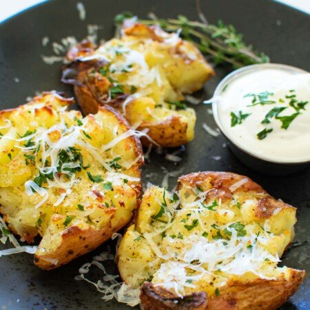 A black plate with cheesy smashed potatoes.