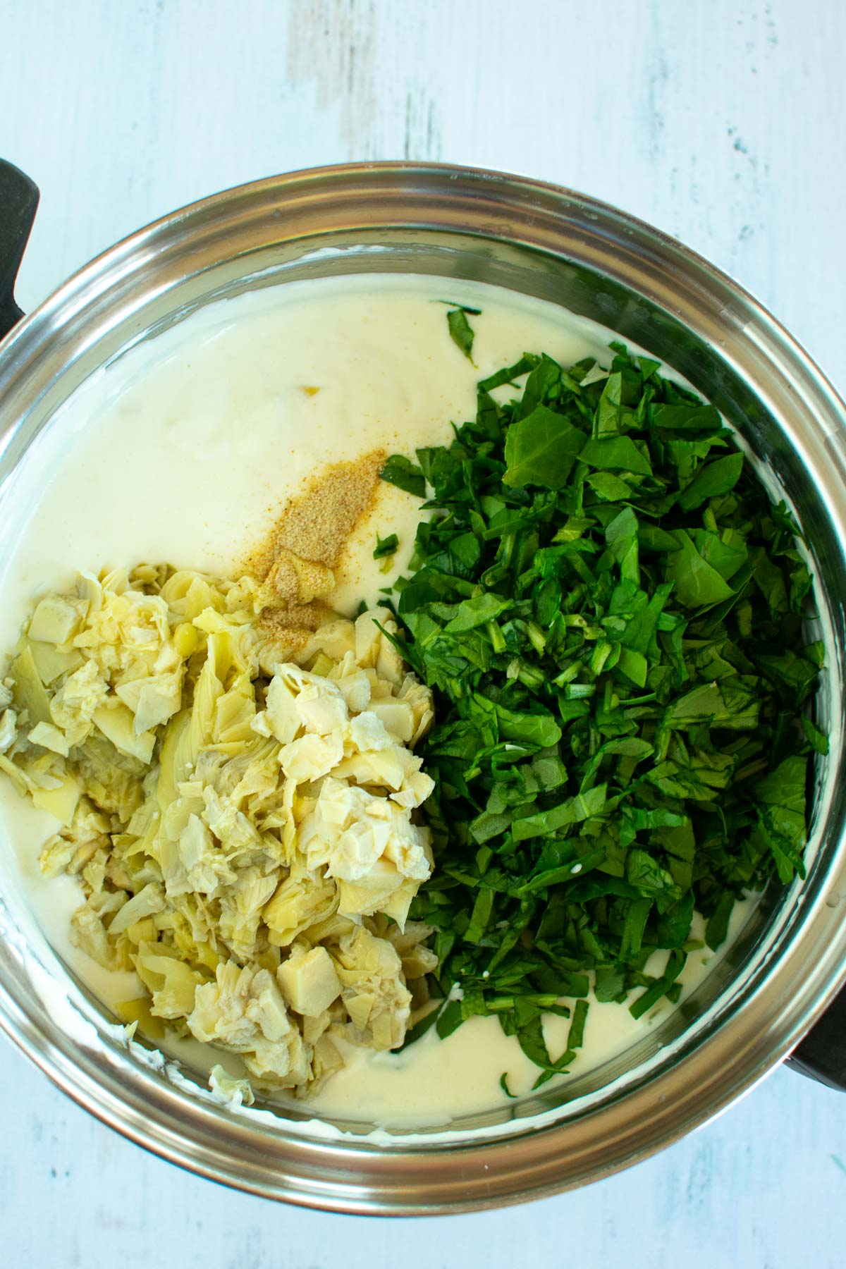 A saucepan with spinach and artichokes in cream sauce.