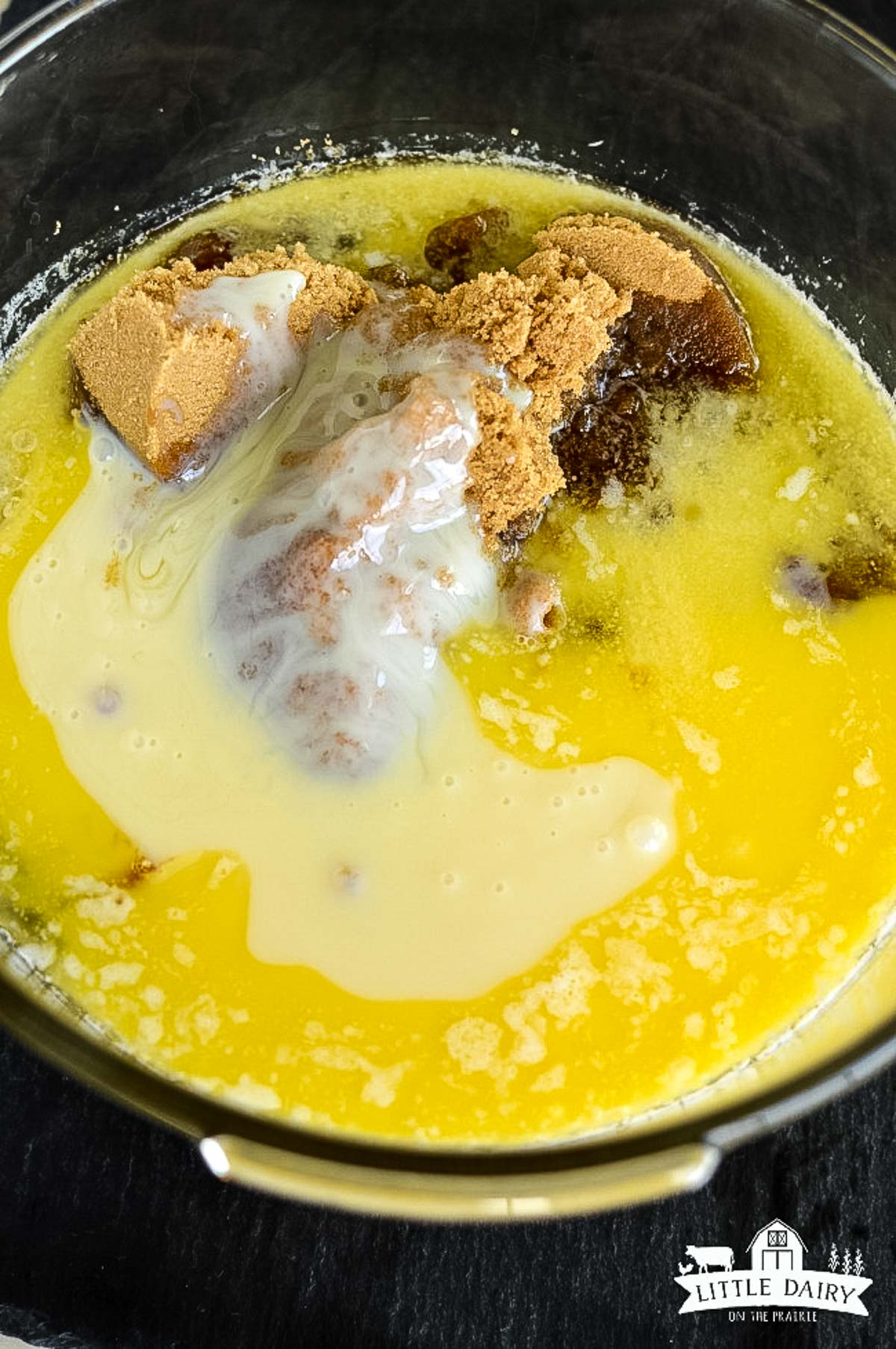 Melted butter, sweetened condensed milk, corn syrup and brown sugar in a glass bowl.