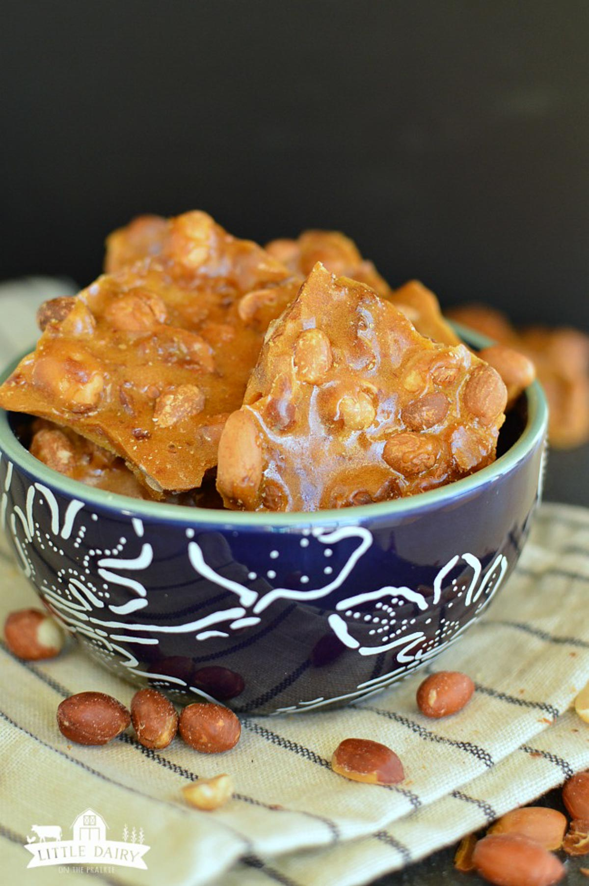 A blue bowl filled with homemade peanut brittle candy.