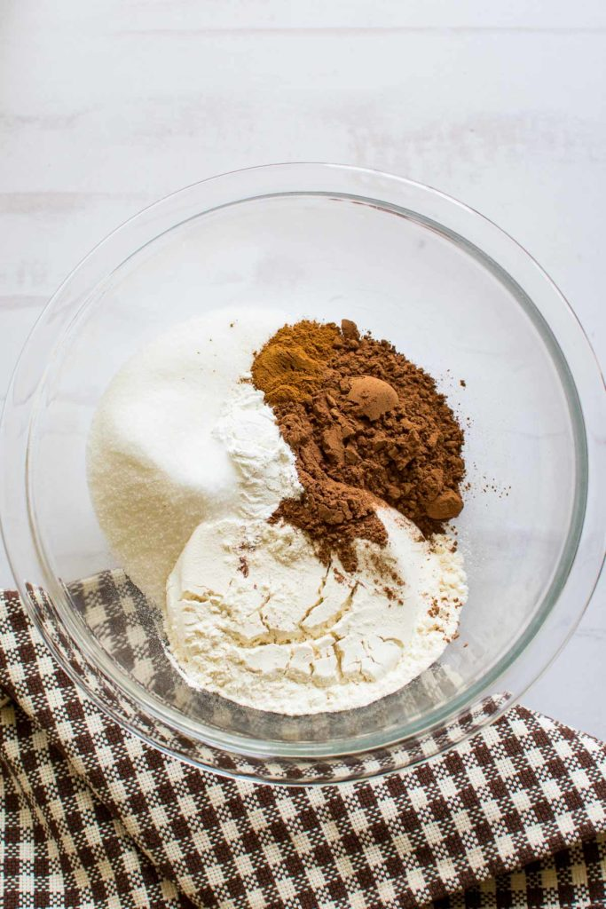 A glass bowl with dry ingredients for making pudding cake