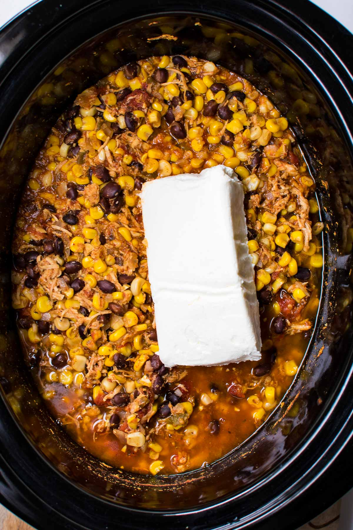 A crock pot with chicken chili and cream cheese.